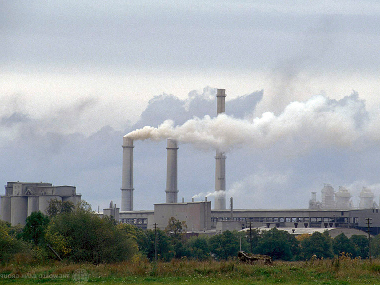 Photograph of a factory with smokestacks