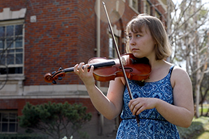 Rose Heising plays the violin outside Hunter Conservatory.
